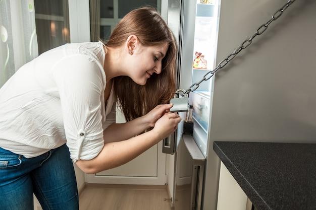 Portret młodej kobiety otwierającej lodówkę zamkniętą łańcuchem