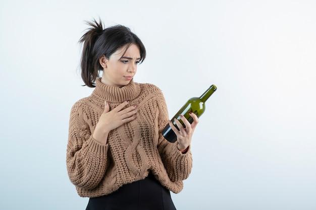 Portret młodej kobiety, patrząc na butelkę wina na białej ścianie