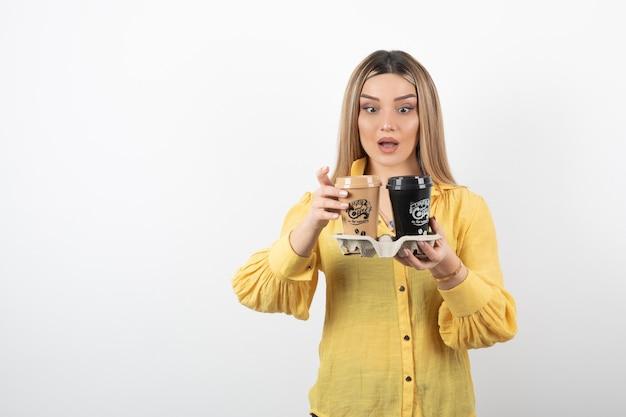 Portret młodej kobiety patrząc na filiżanki kawy na białej ścianie.
