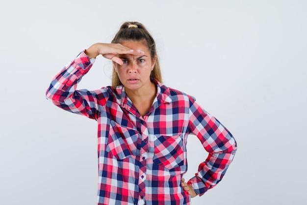 Portret młodej kobiety patrząc na kamery ręką nad głową w koszuli i patrząc skupiony widok z przodu