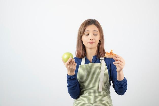 Portret młodej kobiety patrząc na kawałek pizzy i jabłka na białej ścianie.