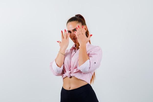 Portret młodej kobiety patrząc przez palce w koszuli, spodniach i patrząc pewnie z przodu