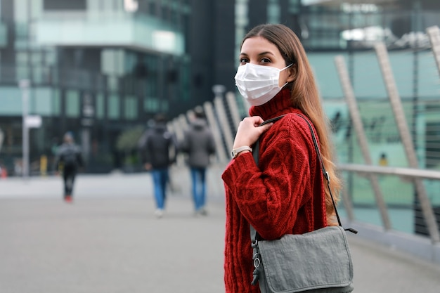Portret młodej kobiety pewnie noszenia maski ochronnej na zewnątrz