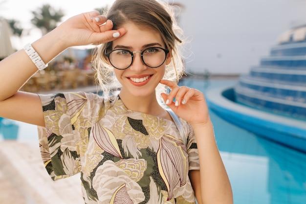 Portret młodej kobiety, piękna dziewczyna w pobliżu ładny basen, hotel spa, ośrodek. dobrze się bawiąc, ciesząc się wakacjami, wakacjami. nosi stylowe okulary, t-shirt, krótki whire manicure, zegarki.
