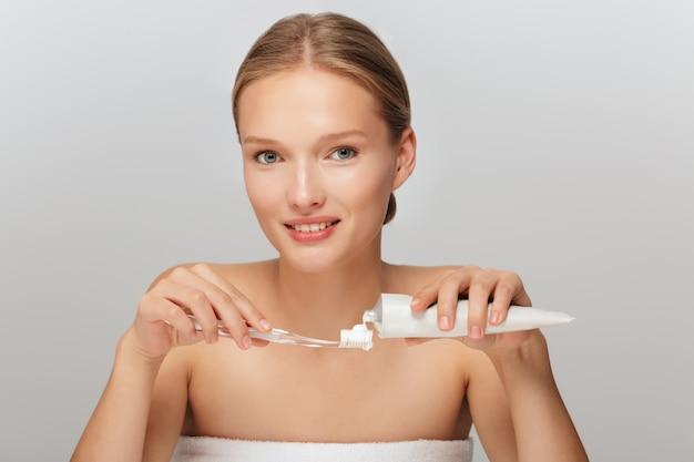 Portret młodej kobiety piękne, bez makijażu, nakładanie pasty do zębów na szczoteczkę