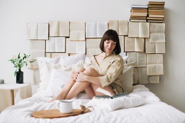 Portret młodej kobiety piękne, czytanie w łóżku w domu.