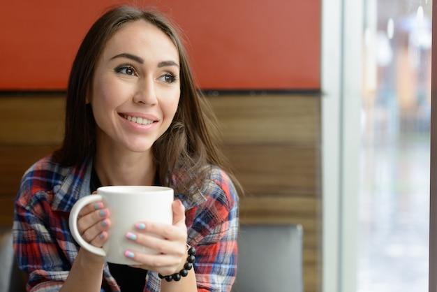 Portret młodej kobiety piękne hipster relaks w pomieszczeniu kawiarni