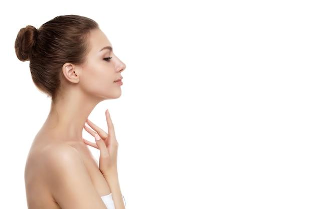 Portret młodej kobiety piękne kaukaski dotykając jej szyi na białym tle. czyszczenie skóry, pielęgnacja skóry, koncepcja kosmetologii. skopiuj miejsce