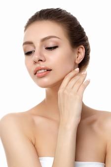Portret młodej kobiety piękne kaukaski dotykając jej szyi na białym tle. czyszczenie skóry, pielęgnacja skóry, koncepcja kosmetologii