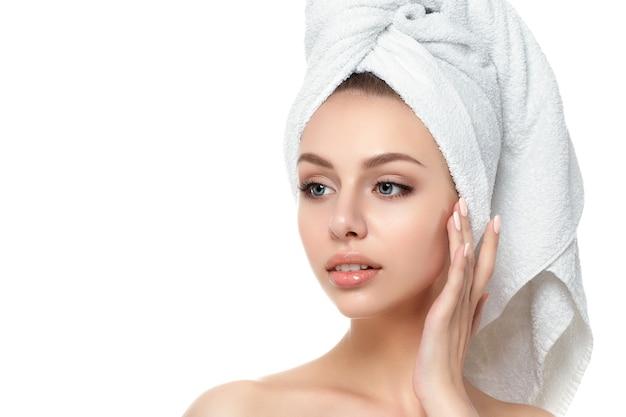 Portret młodej kobiety piękne kaukaski dotykając jej twarzy na białym tle. oczyszczająca twarz, idealna skóra. terapia spa, pielęgnacja skóry, kosmetologia
