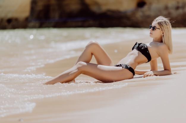 Portret młodej kobiety piękne, leżąc na piasku na plaży oceanu