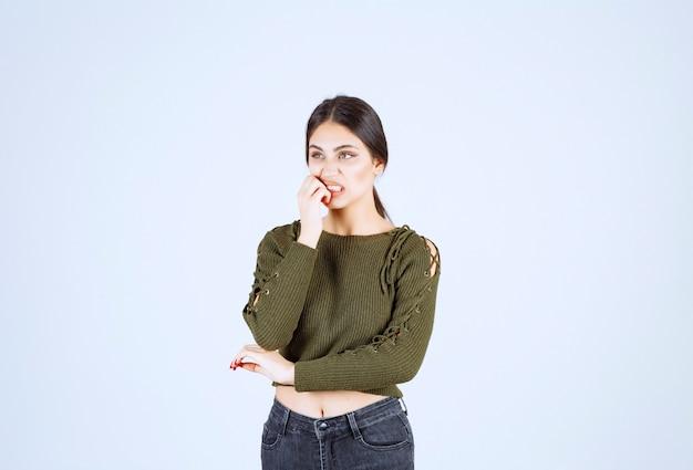 Portret młodej kobiety piękne model stojący i pozowanie na białej ścianie.