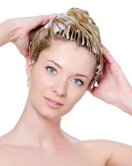 Portret młodej kobiety piękne, mycie włosów - na białym tle