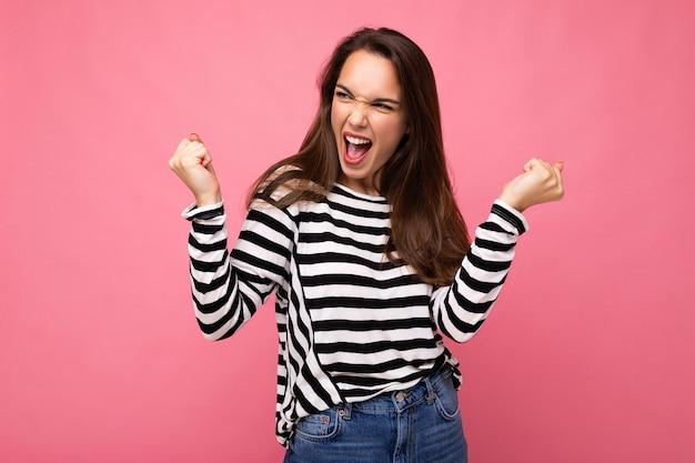 Portret młodej kobiety piękne na sobie luźny sweter w paski i świętuje zwycięstwo krzycząc tak