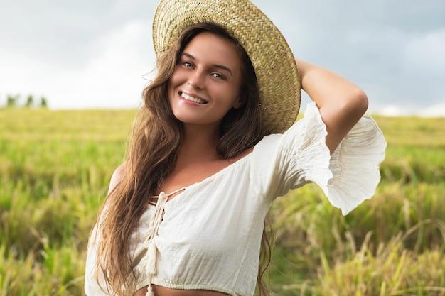 Portret młodej kobiety piękne na sobie słomkowy kapelusz w polu ryżu