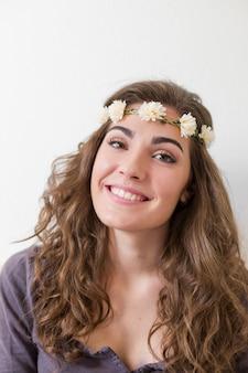 Portret młodej kobiety piękne na sobie wieniec kwiatów. ona uśmiecha się w pomieszczeniu. styl życia. widok pionowy.