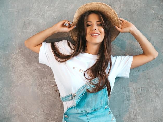 Portret młodej kobiety piękne patrząc. modna dziewczyna w swobodnym letnim kombinezonie ubrania i kapelusz.