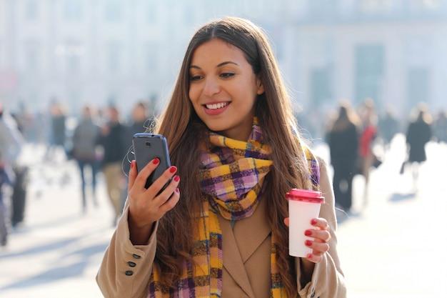 Portret młodej kobiety piękne spaceru na ulicy miasta z telefonem komórkowym i zabrać kawę na świeżym powietrzu z niewyraźnymi ludźmi na ulicy.