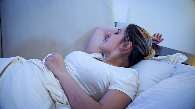Portret młodej kobiety piękne śpi w łóżku w nocy.