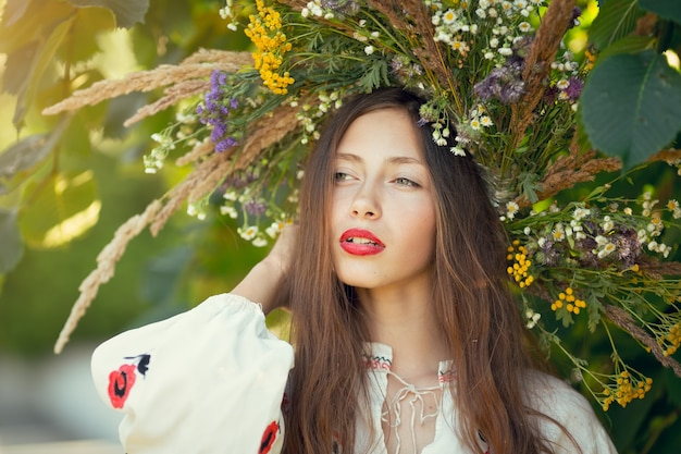 Portret młodej kobiety piękne ubrana w wieniec z dzikich kwiatów. młoda dziewczyna słowiańska