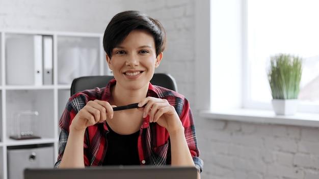 Portret młodej kobiety piękne w casual nosić z laptopem w kreatywnym biurze na poddaszu.