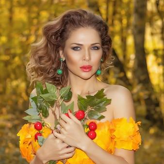 Portret młodej kobiety piękne w sukience z liści jesienią w parku w sezonie jesiennym z bukietem kwiatów w dłoniach. zdjęcie artystyczne