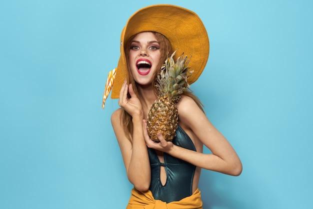 Portret młodej kobiety piękne z ananasem gospodarstwa kapelusz