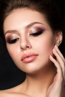 Portret młodej kobiety piękne z wieczorem makijaż dotyka jej twarzy na czarnym tle