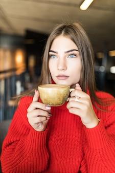 Portret młodej kobiety pijącej kawę przy stole z notatnikiem w kawiarni