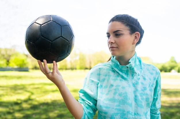 Portret młodej kobiety piłkarz stojący na polu i trzymając piłkę nożną