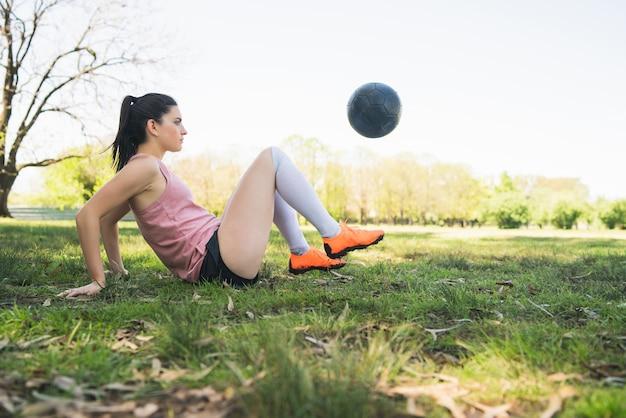 Portret młodej kobiety piłkarz szkolenia i ćwiczenia umiejętności na boisku.