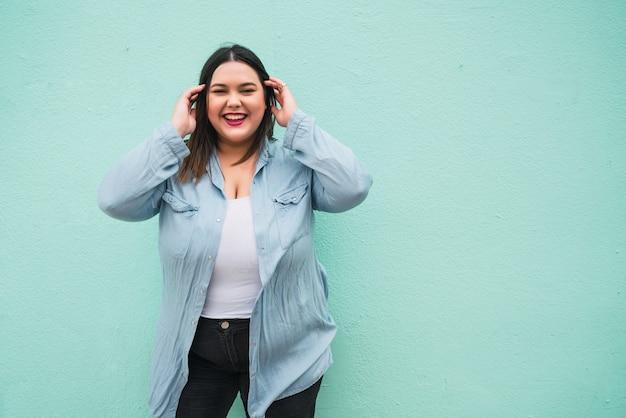 Portret młodej kobiety plus rozmiar uśmiechnięty stojąc na zewnątrz przed jasnoniebieską ścianą.