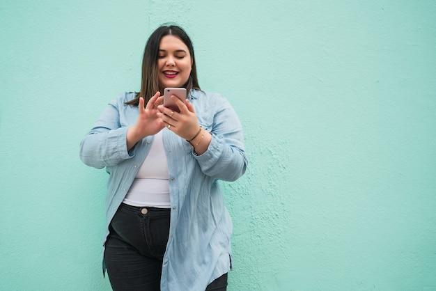Portret młodej kobiety plus rozmiar wpisywanie wiadomości tekstowej na jej telefon komórkowy na zewnątrz. koncepcja technologii.