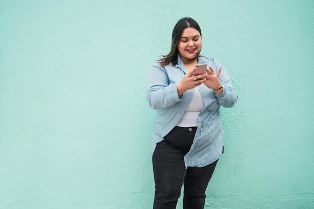 Portret młodej kobiety plus rozmiar wpisywanie wiadomości tekstowej na jej telefon komórkowy na zewnątrz.