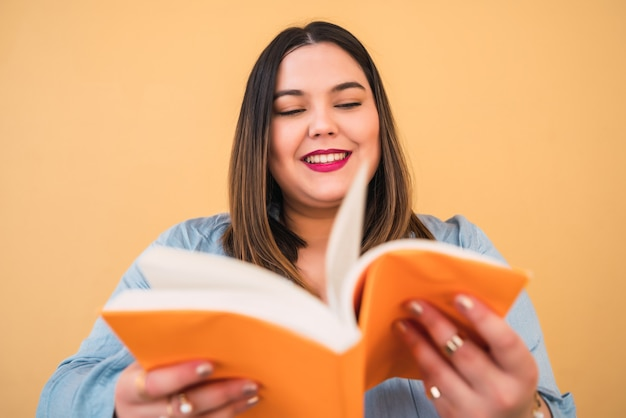 Portret młodej kobiety plus size, ciesząc się wolnym czasem i czytając książkę