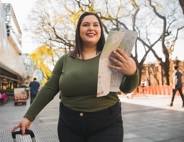 Portret młodej kobiety plus size trzyma mapę i szuka wskazówek na zewnątrz na ulicy. koncepcja podróży.