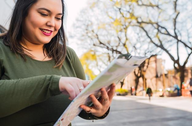 Portret młodej kobiety plus size trzymającej mapę i szukającej wskazówek na zewnątrz na ulicy.
