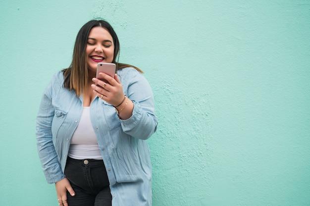 Portret młodej kobiety plus size uśmiecha się podczas pisania wiadomości tekstowej na swoim telefonie komórkowym na zewnątrz. koncepcja technologii.