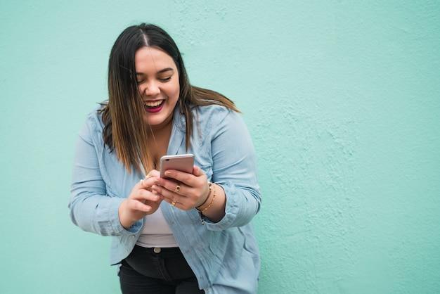 Portret młodej kobiety plus size uśmiecha się podczas pisania wiadomości tekstowej na swoim telefonie komórkowym na zewnątrz