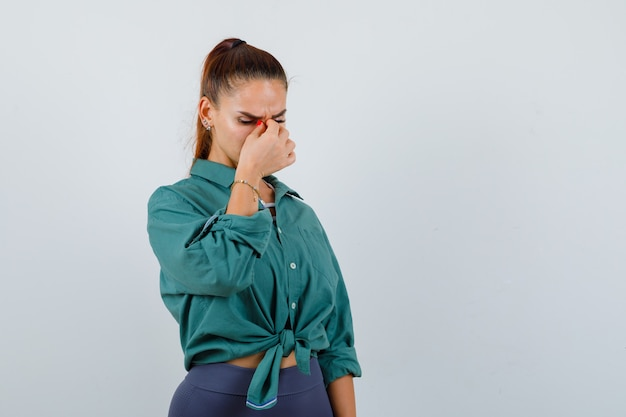 Portret młodej kobiety pocierającej oczy i nos w zielonej koszuli i patrzącej na zmęczonego widoku z przodu