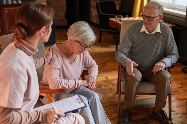 Portret młodej kobiety pocieszająca starsza pani podczas sesji terapeutycznej w domu starców, kopia przestrzeń