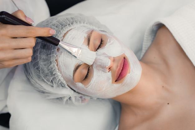 Portret młodej kobiety podczas zabiegu kosmetycznego twarzy w salonie spa