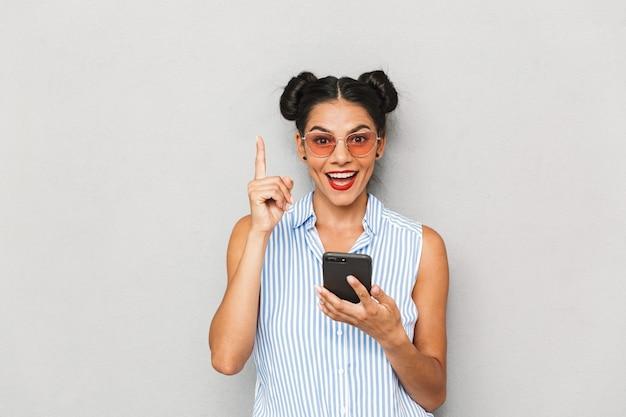 Portret młodej kobiety podekscytowany w okulary na białym tle, przy użyciu telefonu komórkowego