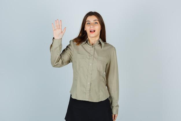 Portret młodej kobiety pokazano dłoń w koszuli, spódnicy i patrząc zdziwiony widok z przodu