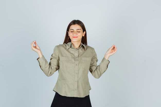 Portret młodej kobiety pokazano gest jogi z zamkniętymi oczami w koszuli