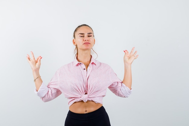 Portret młodej kobiety pokazano gest medytacji w przypadkowej koszuli i patrząc spokojny widok z przodu