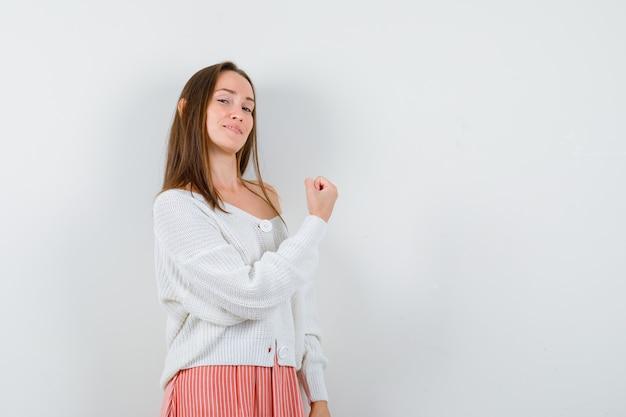 Portret młodej kobiety pokazano gest zwycięzcy w kardigan na białym tle