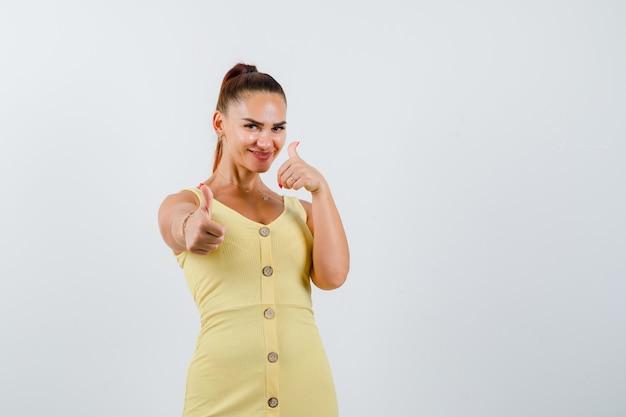 Portret młodej kobiety pokazano podwójne kciuki w żółtej sukience i patrząc szczęśliwy widok z przodu
