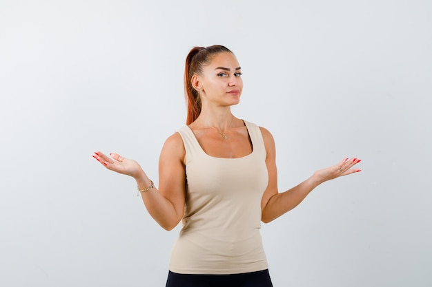 Portret młodej kobiety pokazując bezradny gest w beżowym podkoszulku bez rękawów i patrząc nieświadomy widok z przodu