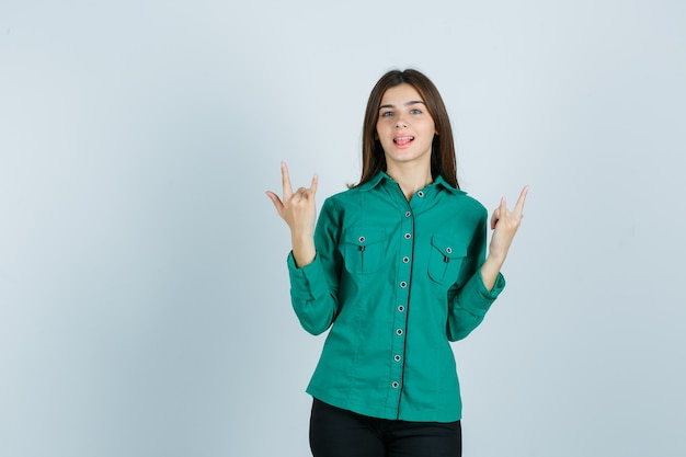 Portret młodej kobiety pokazując gest rocka, wystający język w zielonej koszuli i patrząc szczęśliwy widok z przodu